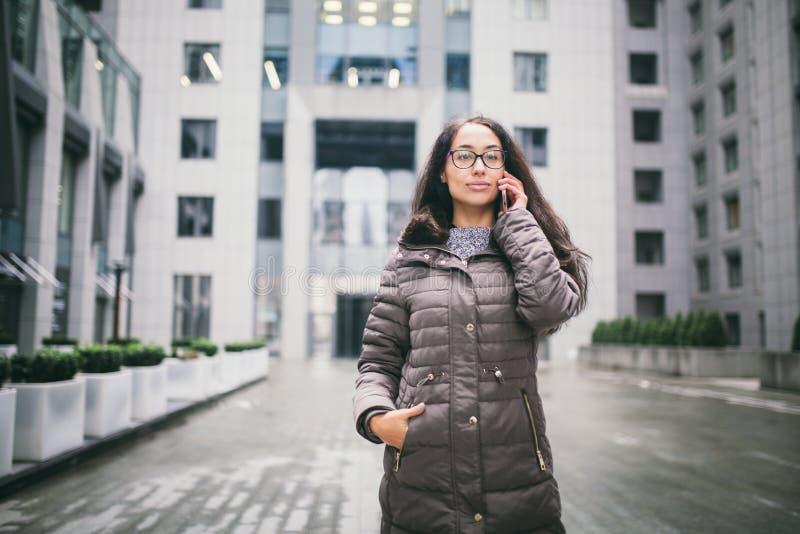 Thema ist die Geschäftslage Schöne junge Frau der europäischen Ethnie mit den tragenden Gläsern und Mantel des langen Brunettehaa lizenzfreie stockfotos