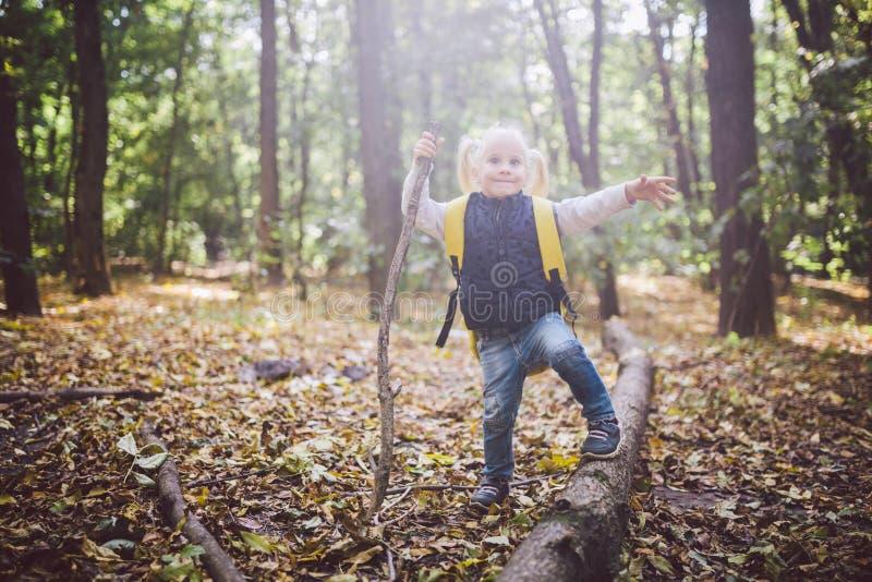 Thema openluchtactiviteiten in aard Grappig loopt weinig Kaukasisch blondemeisje gangen wandelend in het bos op ruw terrein met a royalty-vrije stock foto