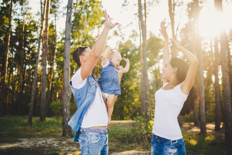 Themafamilienurlaub im kleinen Kind des Wald A hat Tochter mit Vati auf Schultern, hoben Mutterstände nahe bei ihr Arme an und stockfotografie