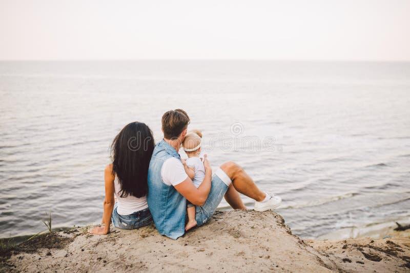 Themafamilienurlaub mit kleinem Kind auf der Natur und dem Meer Mutter, Vati und Tochter von einem Jahr sitzen in der Umarmung, M lizenzfreie stockfotos