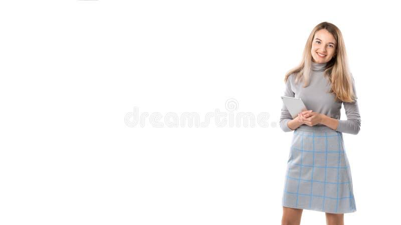 ThemaGeschäftsfrautechnologie Schöne junge kaukasische blonde Frau im grauen Kleid, das Stellung mit den Tablettenhänden auf Weiß stockfoto