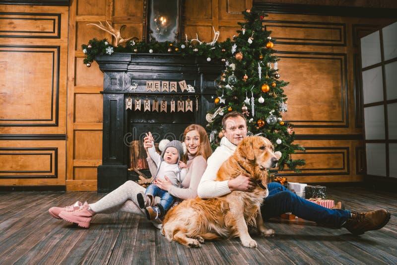 Themakerstmis en de cirkel van de Nieuwjaarfamilie Jonge Kaukasische familie met 1 van het de hondras van het éénjarigenkind Gold stock foto