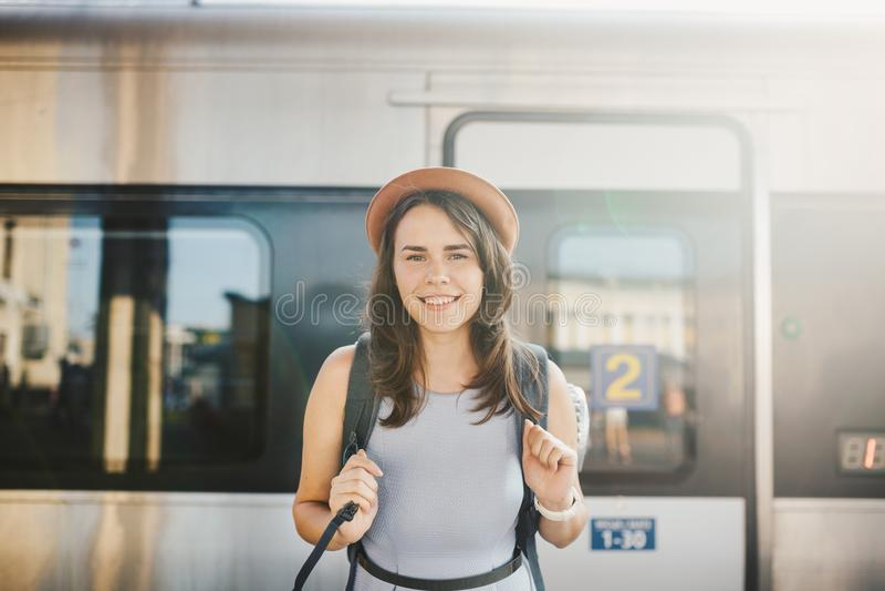 Themaspoorweg en reis Portret jonge Kaukasische vrouw met toothy glimlach die zich bij de achtergrond van de stationtrein met bac stock afbeelding