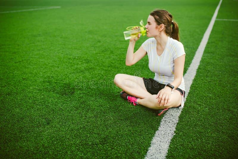 Themasport en gezondheid Mooie jonge meisjeszitting die op groen gras, kunstmatig grasstadion rusten die dorstige drankfles ruste royalty-vrije stock foto's