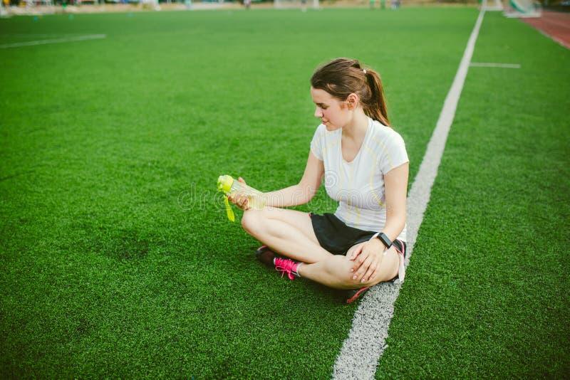 Themasport und -gesundheit Schönes sitzendes Stillstehen des jungen Mädchens auf grünem Gras, künstliches Rasenstadion, das durst stockfotografie