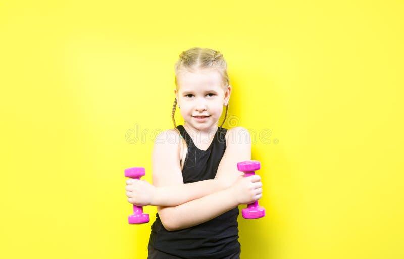 Themasport und -gesundheit Sch?nes kaukasisches Kinderm?dchen mit den Z?pfen, die auf gelbem Hintergrund mit L?cheln aufwerfen kl stockfotografie