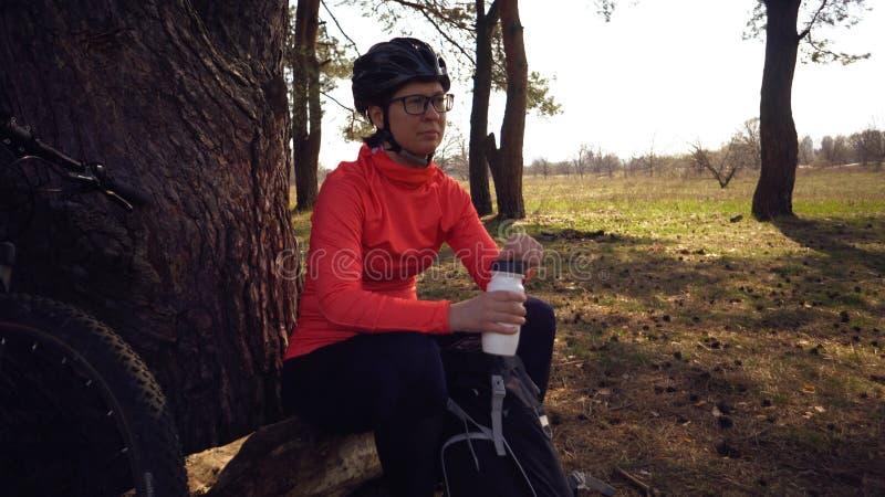 Themasporten en toerisme in aard Kaukasische jonge vrouwenfietser in een helm en een sportkleding die een bergfiets in het bos be royalty-vrije stock afbeeldingen