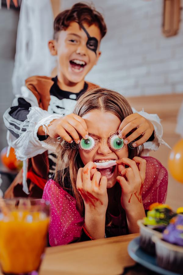 Brother and children feeling funny while eating thematic sweets for Halloween. Thematic sweets. Brother and children feeling extremely funny while eating stock photography