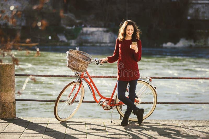 Thematoerisme op fiets en moderne technologie De mooie jonge Kaukasische vrouw bevindt zich dichtbij rode retro fiets op rivieroe stock foto's