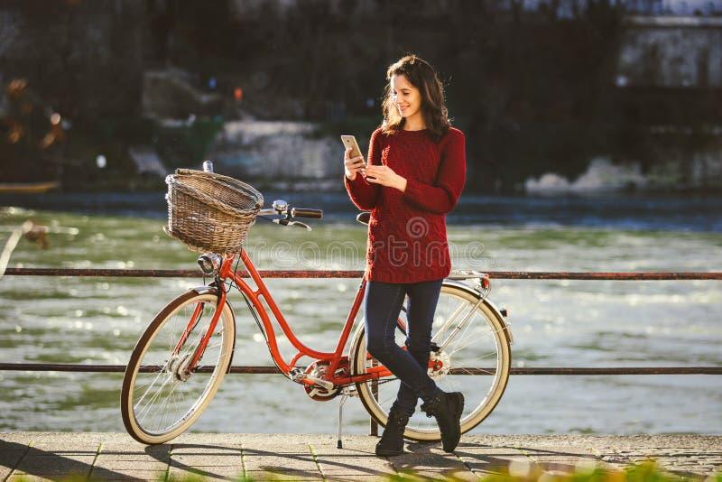 Thematoerisme op fiets en moderne technologie De mooie jonge Kaukasische vrouw bevindt zich dichtbij rode retro fiets op rivieroe royalty-vrije stock afbeelding
