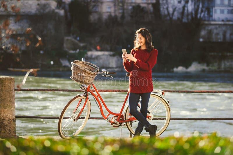 Thematoerisme op fiets en moderne technologie De mooie jonge Kaukasische vrouw bevindt zich dichtbij rode retro fiets op rivieroe stock afbeeldingen