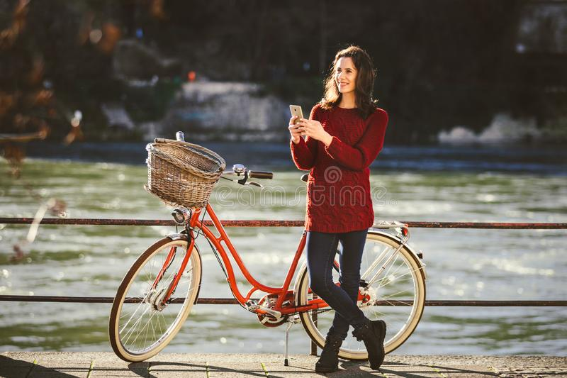 Thematoerisme op fiets en moderne technologie De mooie jonge Kaukasische vrouw bevindt zich dichtbij rode retro fiets op rivieroe stock fotografie