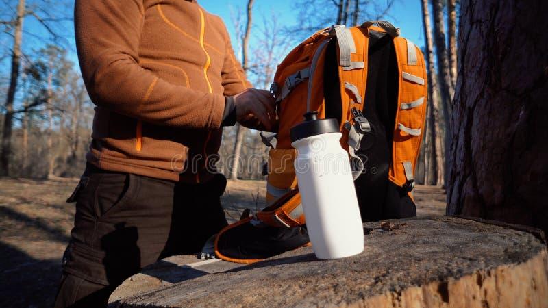 Themawandern und -reise Ein kaukasischer touristischer Mann packt einen orange Rucksack aus, nimmt seine Sachen heraus und setzt  lizenzfreies stockfoto