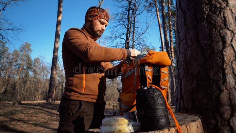 Themawandern und -reise Ein kaukasischer touristischer Mann packt einen orange Rucksack aus, nimmt seine Sachen heraus und setzt  stockbild