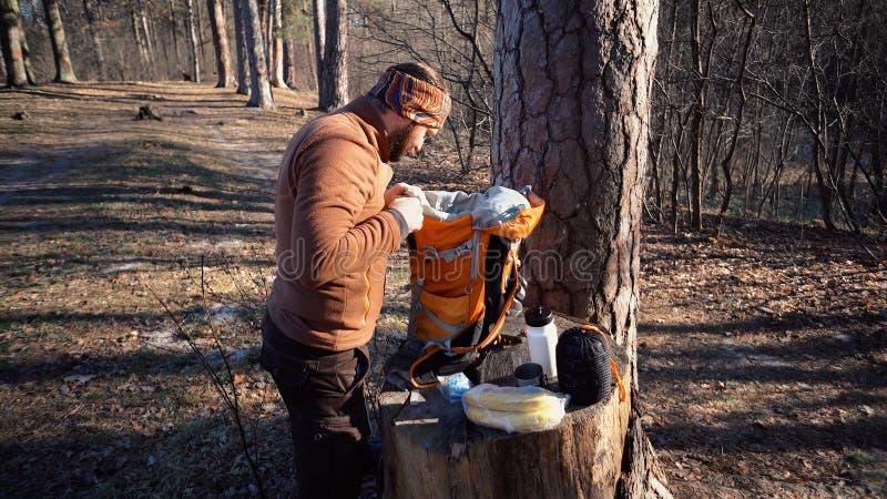 Themawandern und -reise Ein kaukasischer touristischer Mann packt einen orange Rucksack aus, nimmt seine Sachen heraus und setzt  lizenzfreie stockfotos