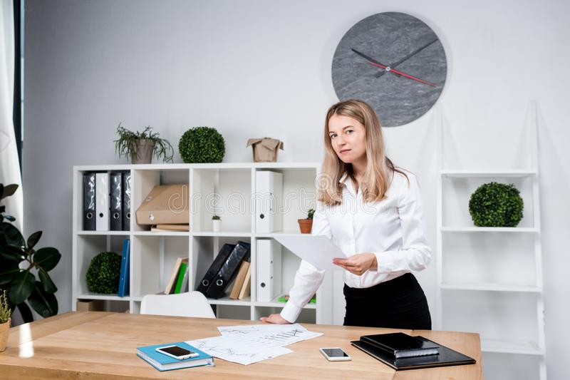 Theme business woman at work. Beautiful young caucasian woman business man working standing in the office near the table, checks stock photo