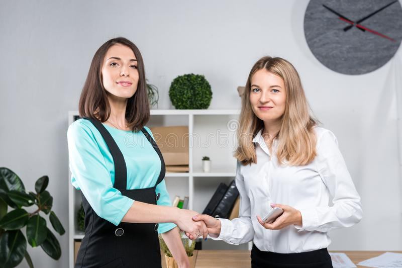 Theme business women. Two young Caucasian women business partners in formal clothes sign a contract, making a deal a handshake in stock image