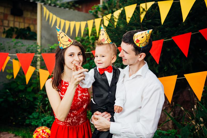 Theme children birthday party. Family father and mother holding son of one year on the background of greenery and festive decor, g stock image