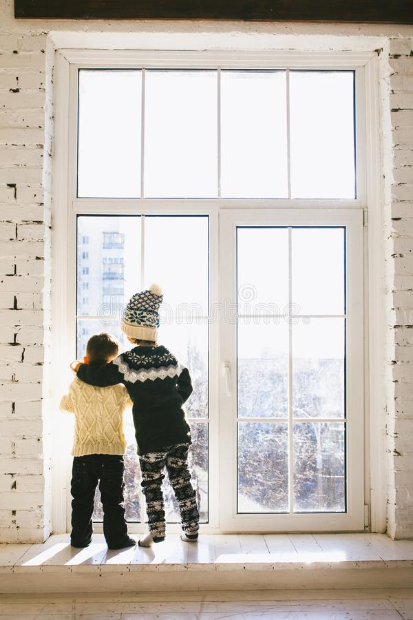 Theme Christmas morning. Two baby Caucasian boy and girl brother and sister standing with backs on window front of large box in em stock images