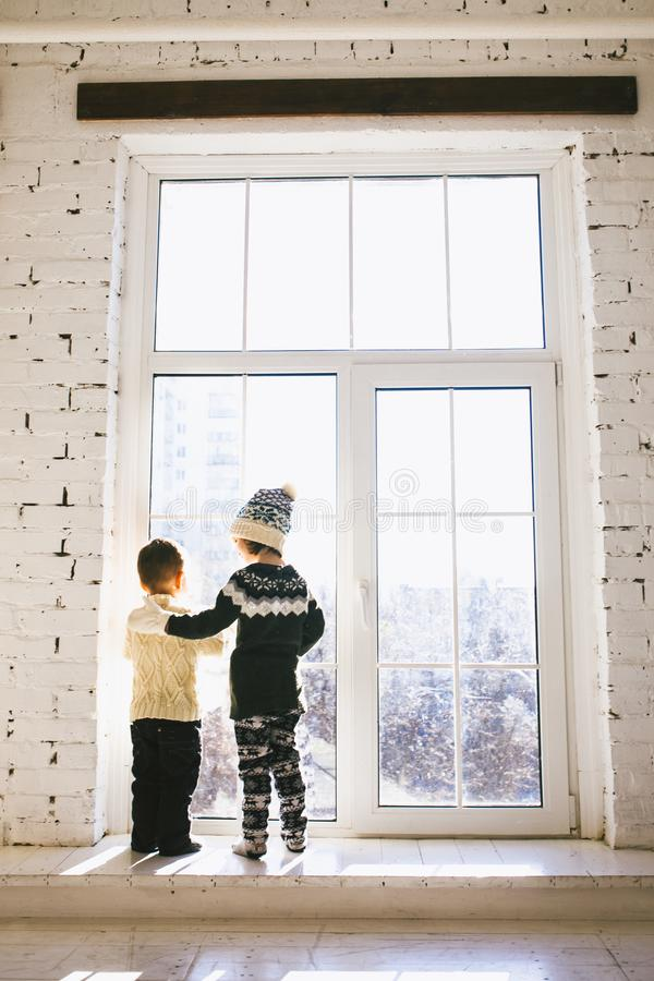 Theme Christmas morning. Two baby Caucasian boy and girl brother and sister standing with backs on window front of large box in em royalty free stock image