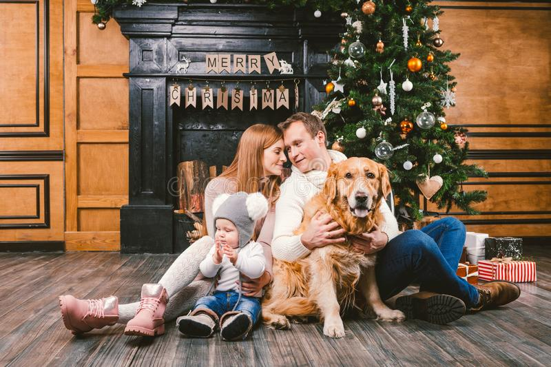 Theme Christmas and New Year family circle. Young Caucasian family with 1 year old child dog breed Labrador Golden Retriever. Sitting on wooden floor home in royalty free stock photography