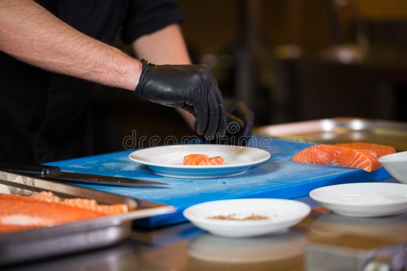 Theme cooking is a profession of cooking. Close-up of a Caucasian man`s hand in a restaurant kitchen preparing red fish fillets royalty free stock images