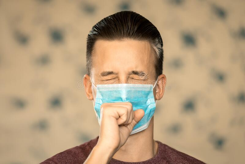 Theme of coronavirus and safety. A young man in a blue virus mask coughs into a fist. Horizontal frame. Theme of coronavirus and safety. A young man in a blue stock images