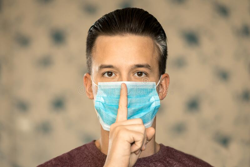 Theme of coronavirus and safety. A young man in a blue virus mask shows his finger a sign of silence. Horizontal frame. Theme of coronavirus and safety. A young stock photography