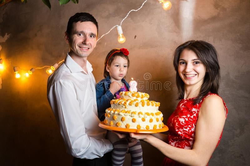 Theme family holiday childrens birthday and blowing out candles on large cake. young family of three people standing and. Holding 3 year old daughter in yard stock photos