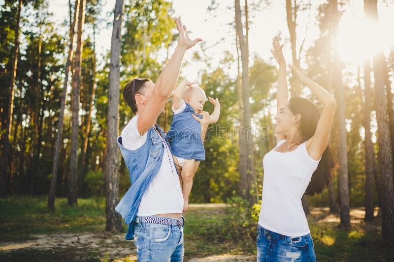 Theme family vacation in the forest. A small child has daughter with daddy on shoulders, mother stands next to her raised arms and. Smile. Dad and mom playing stock photography