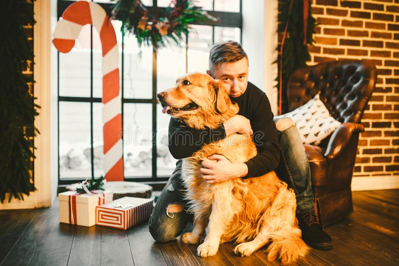 The theme is the friendship of man and animal. Caucasian young male and pet dog breed Labrador Golden Retriever at home inside in stock photography