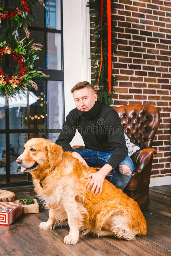 The theme is the friendship of man and animal. Caucasian young male and pet dog breed Labrador Golden Retriever at home inside in royalty free stock photo