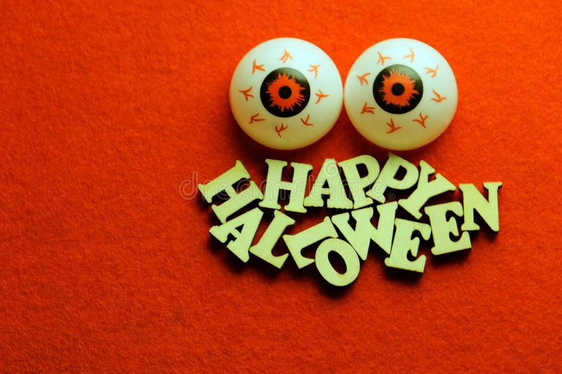 Inscription HAPPY HALLOWEEN with eyes from chaotically lying wooden letters on a red background. Copy space. Theme for the holiday. Theme for the holiday All stock image