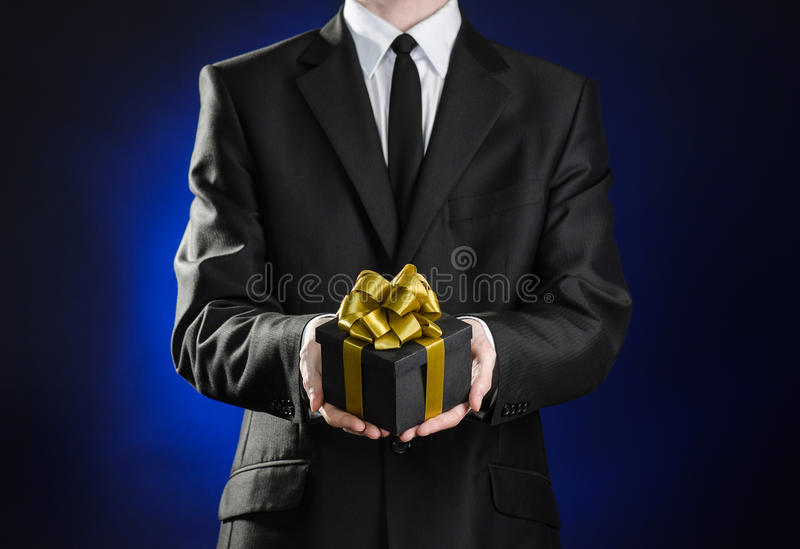 Theme holidays and gifts: a man in a black suit holds exclusive gift wrapped in a black box with gold ribbon and bow on a dark. Blue background stock images