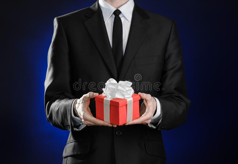 Theme holidays and gifts: a man in a black suit holds exclusive gift wrapped in red box with white ribbon and bow on a dark blue royalty free stock photos