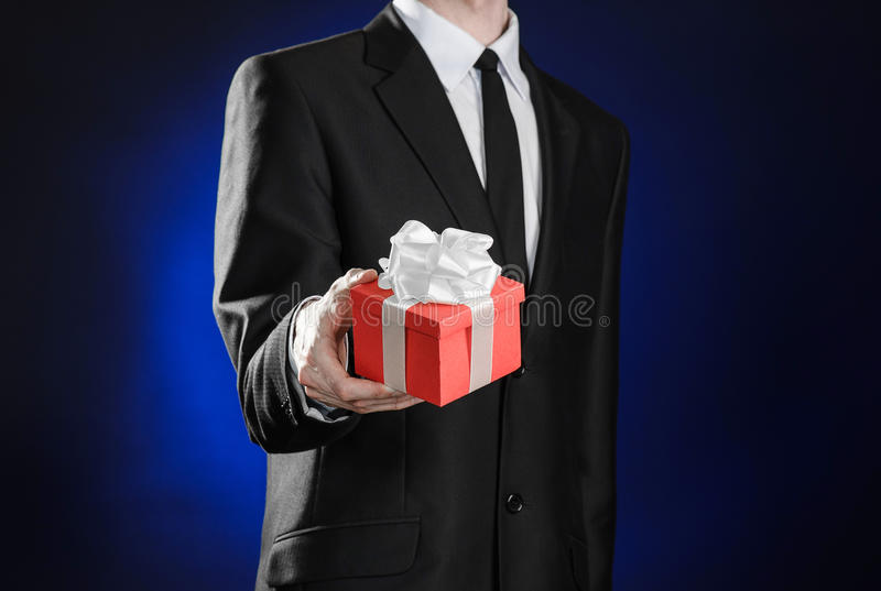 Theme holidays and gifts: a man in a black suit holds exclusive gift wrapped in red box with white ribbon and bow on a dark blue stock photography