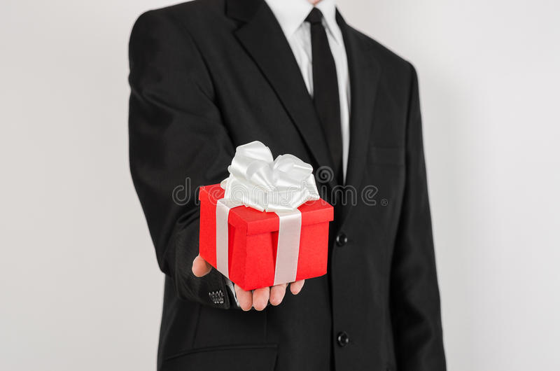 Theme holidays and gifts: a man in a black suit holds exclusive gift wrapped in red box with white ribbon and bow isolated on a royalty free stock image