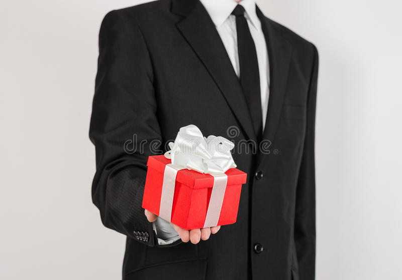 Theme holidays and gifts: a man in a black suit holds exclusive gift wrapped in red box with white ribbon and bow isolated on a stock image