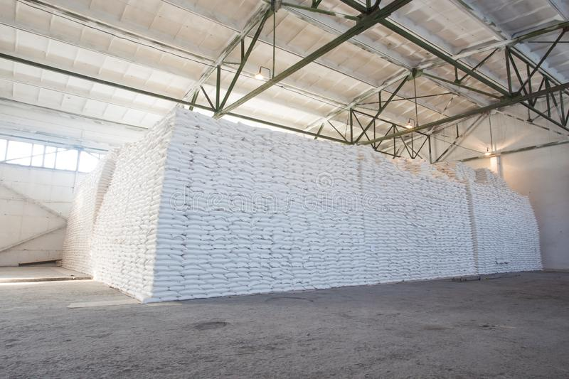 Theme industry and economics, stocks in stock.A lot of white fabric bags with loose products stacked in piles indoors at the royalty free stock photography