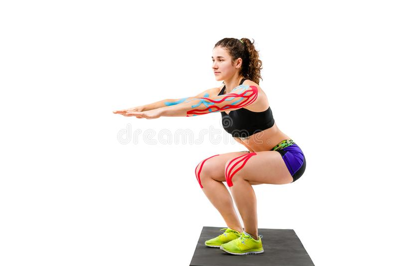 Theme kinesiology tape rehabilitation and health of athletes. Beautiful girl doing a squat exercise on a black rug on a white isol stock photography