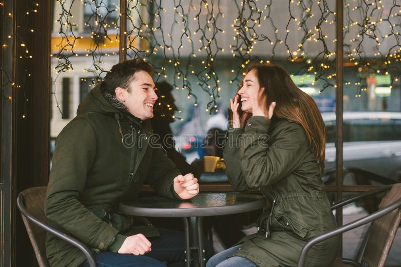 Theme love holiday Valentines Day. pair college students, Caucasian heterosexual lovers in winter, sit table of street stock image