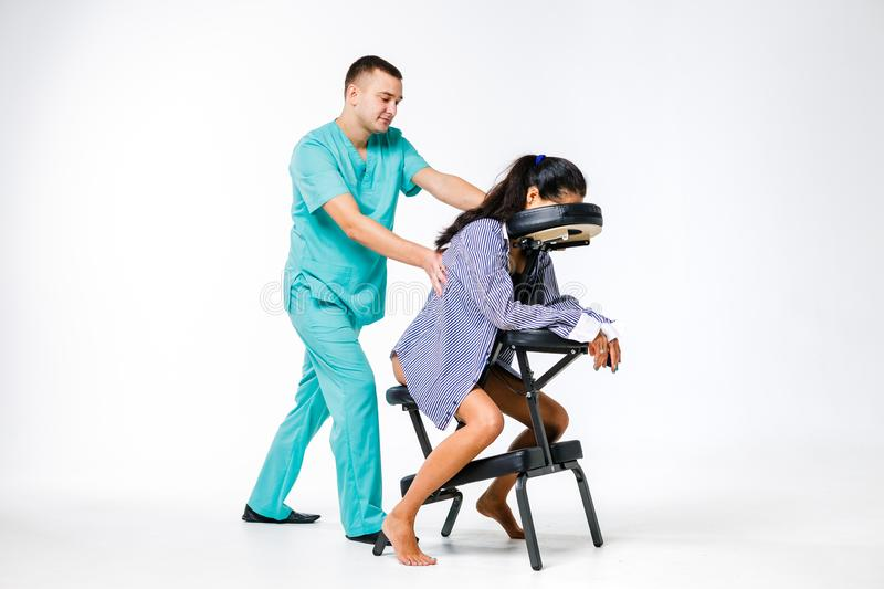 Theme massage and office. Male therapist with blue suit doing back and neck massage for young woman worker, business woman in shir stock photos
