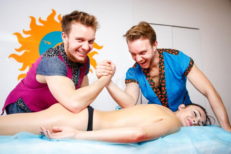 Theme medicine and rehabilitation. two twin brothers Young male doctor masseur treats massaging a young woman on a massage table. Theme medicine and stock photos