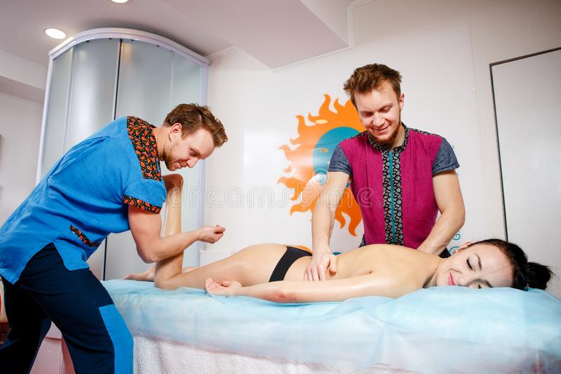 Theme medicine and rehabilitation. two twin brothers Young male doctor masseur treats massaging a young woman on a massage table. Theme medicine and stock photography