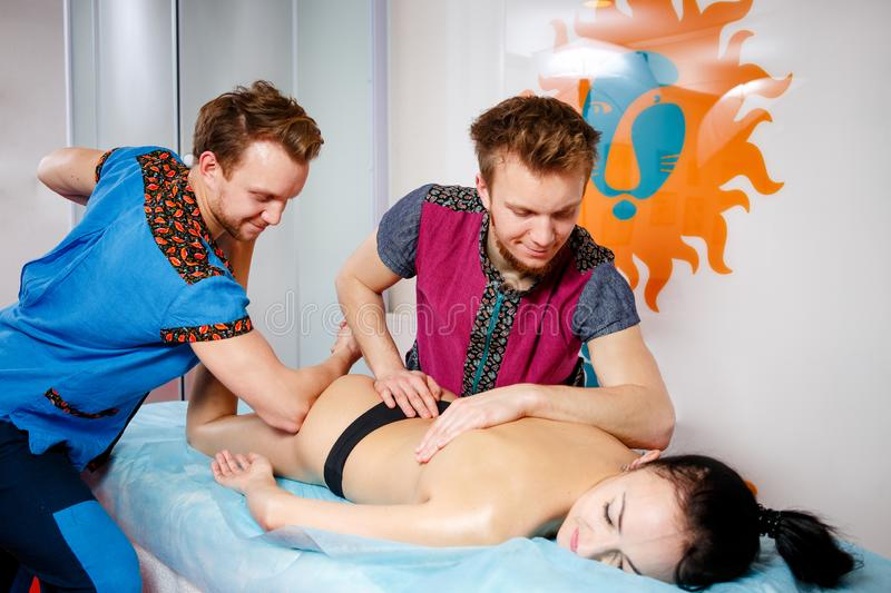 Theme medicine and rehabilitation. two twin brothers Young male doctor masseur treats massaging a young woman on a massage table. Theme medicine and royalty free stock photo