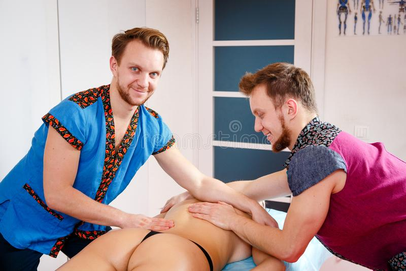 Theme medicine and rehabilitation. two twin brothers Young male doctor masseur treats massaging a young woman on a massage table. Theme medicine and royalty free stock image