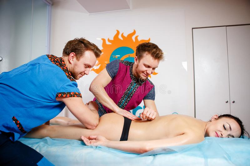 Theme medicine and rehabilitation. two twin brothers Young male doctor masseur treats massaging a young woman on a massage table. Theme medicine and stock images