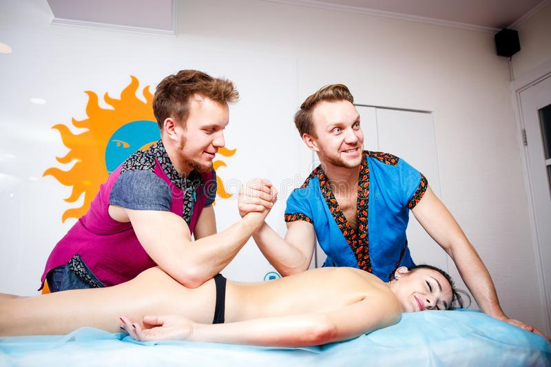 Theme medicine and rehabilitation. two twin brothers Young male doctor masseur treats massaging a young woman on a massage table. Theme medicine and stock photo
