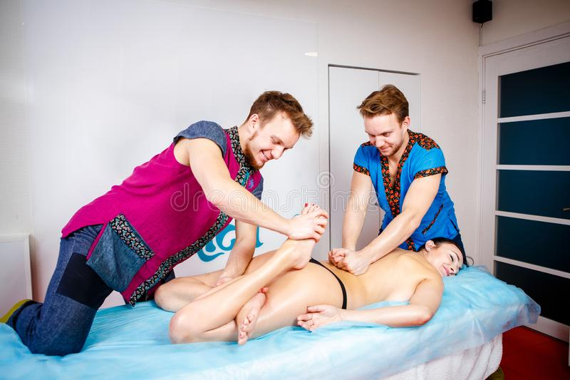 Theme medicine and rehabilitation. two twin brothers Young male doctor masseur treats massaging a young woman on a massage table. Theme medicine and royalty free stock images