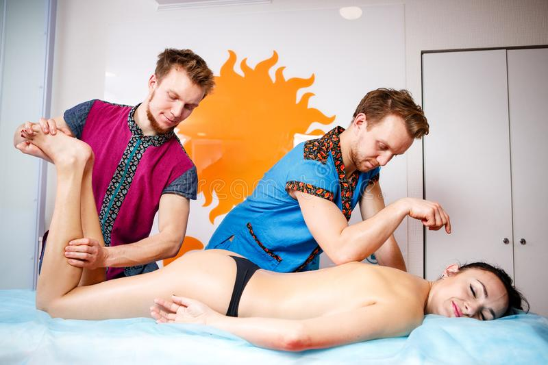 Theme medicine and rehabilitation. two twin brothers Young male doctor masseur treats massaging a young woman on a massage table. Theme medicine and royalty free stock photography